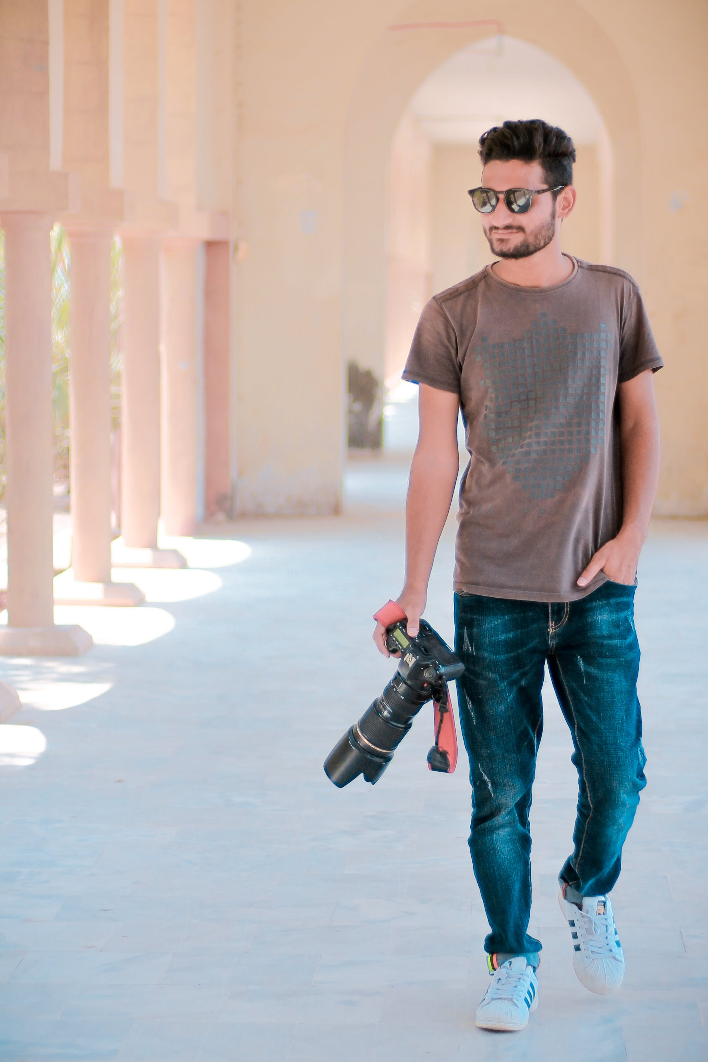 Man Walking On Hallway While Holding Dslr Camera