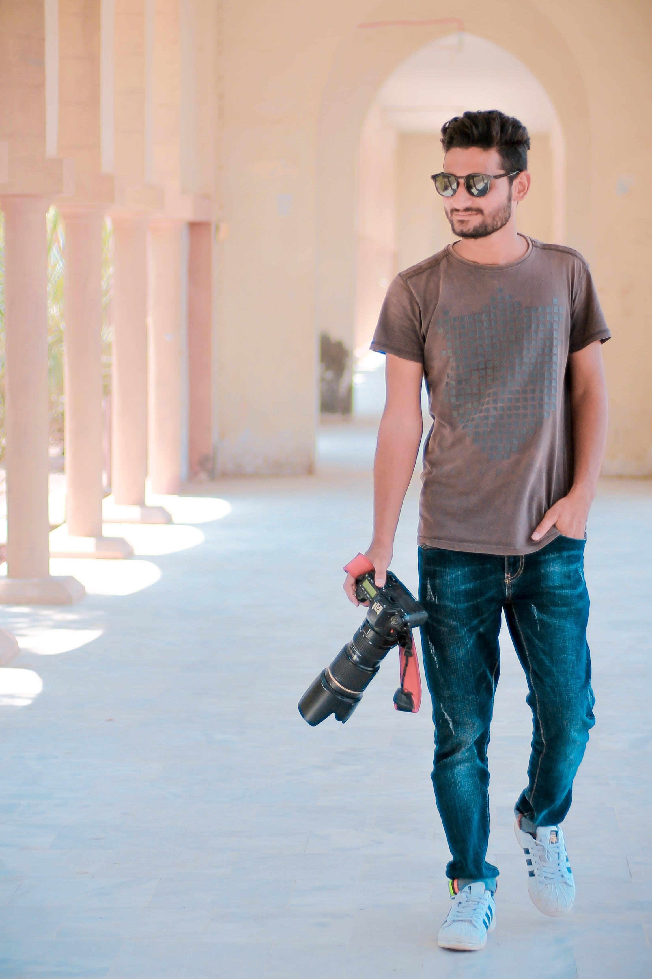 Man Walking On Hallway While Holding Dslr Camera