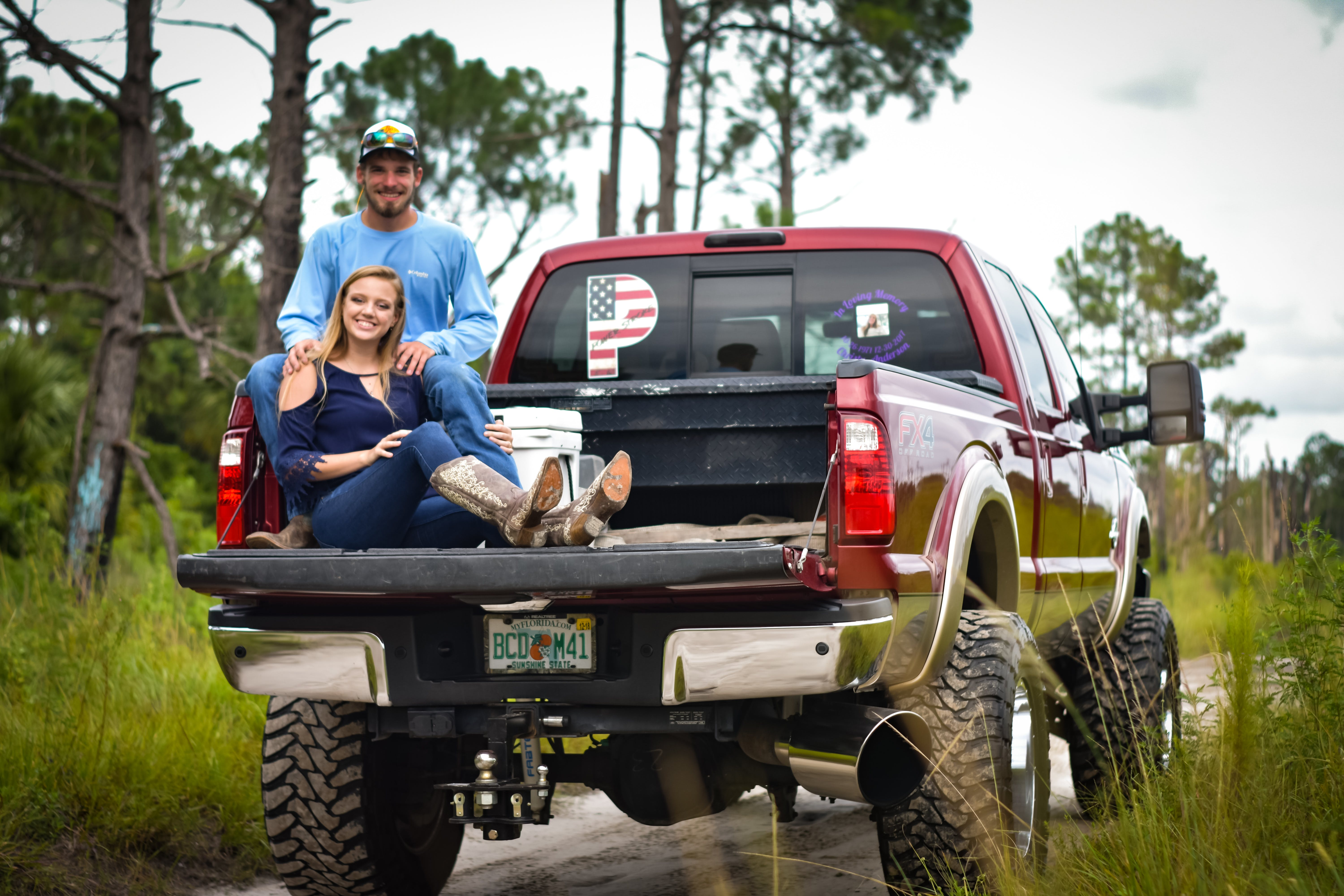Man And Woman Sitting On Back Of Pickup Truck