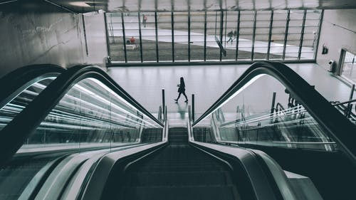 Grayscale Photography of Person Walking Near Escalator