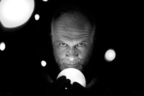 Grayscale Photo Of Man Holding Light