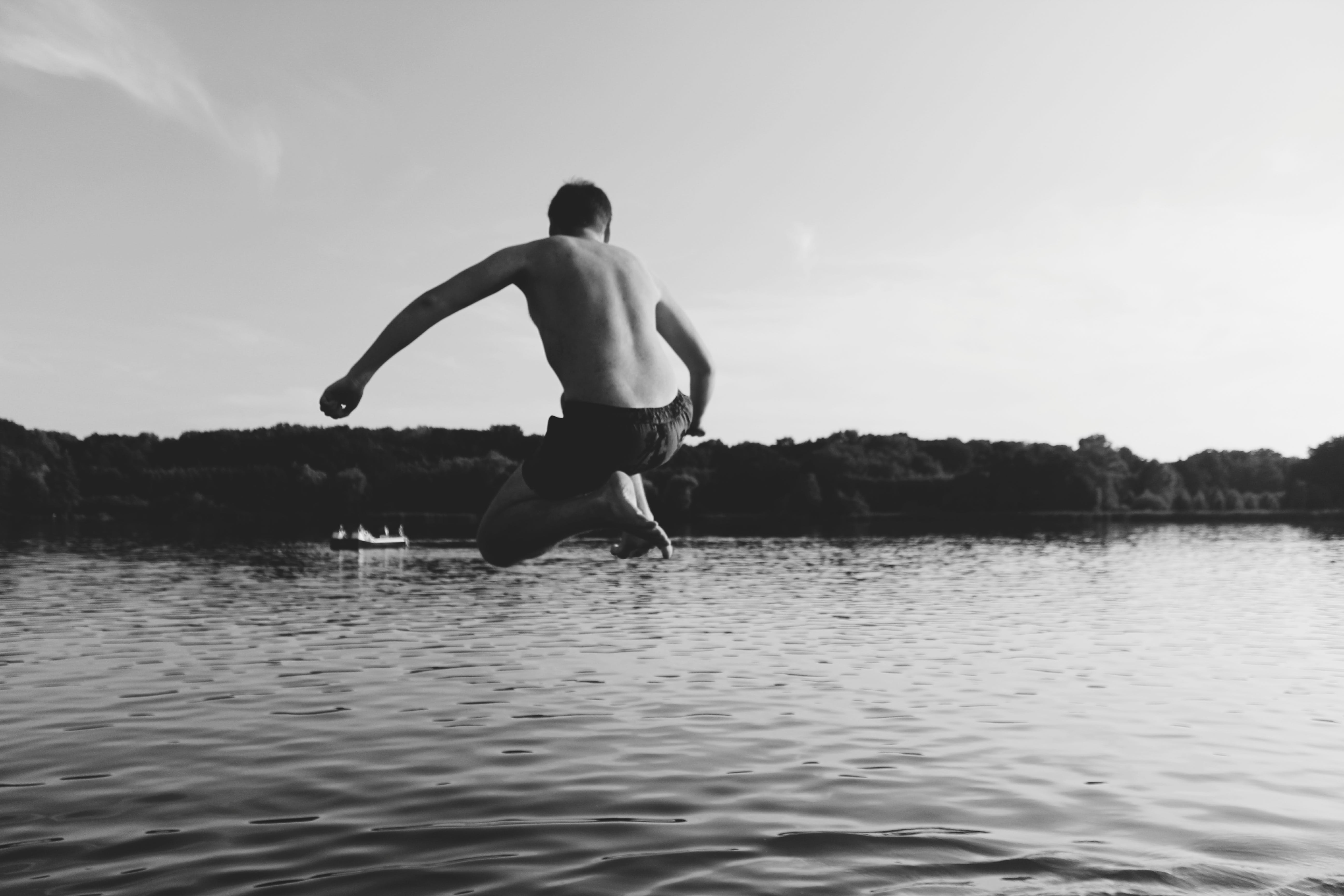 Monochrome Photography of Man Jumping into The Water