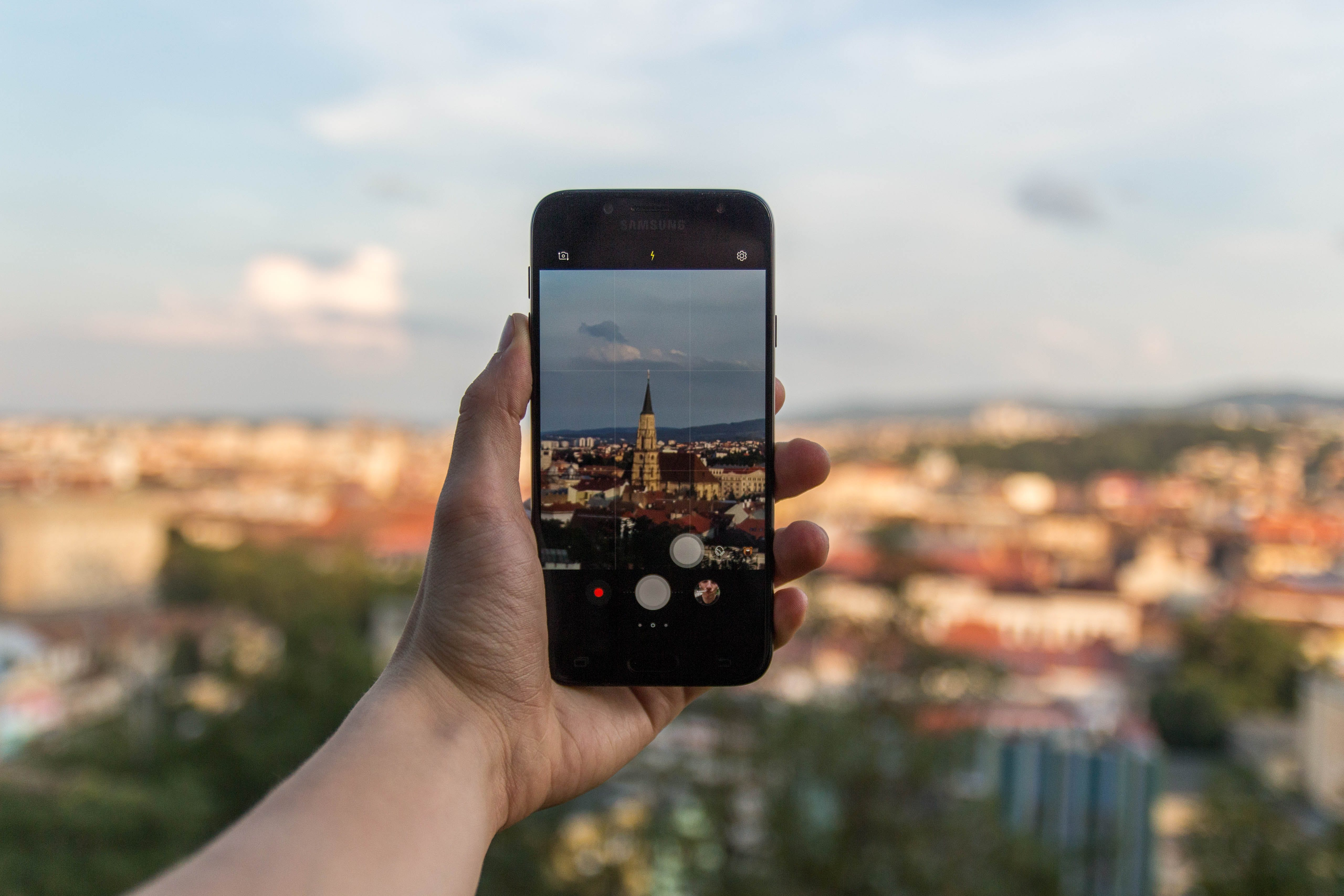Person Taking Picture of Beige Building Using Black Smartphone