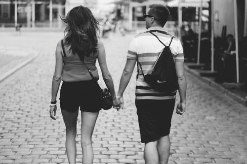 Grayscale Photography Of Man And Woman Holding Hands While Walking