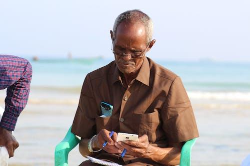 Foto profissional grátis de homem idoso, smartphone