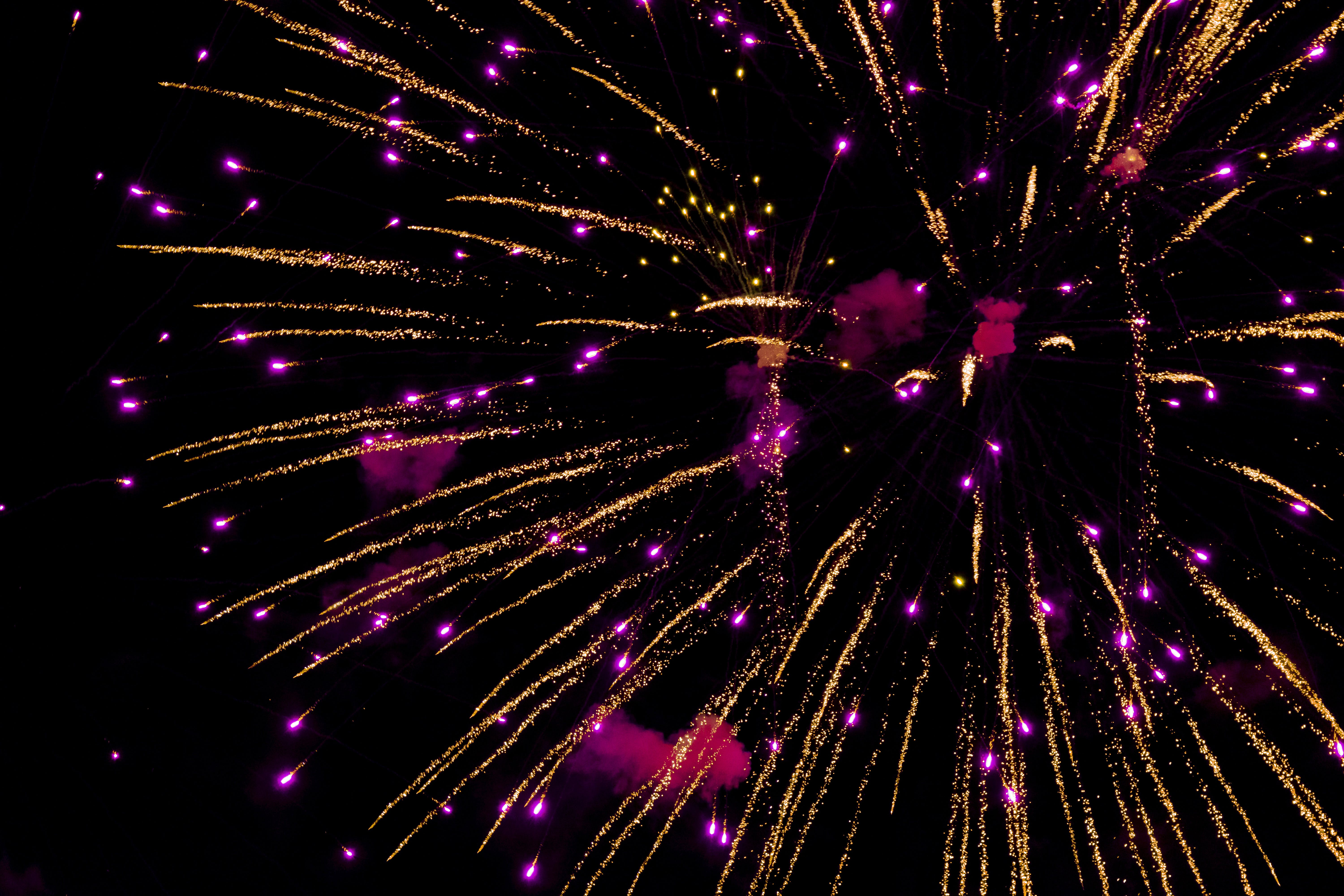 Photo of Purple and Yellow Fireworks in Night Sky