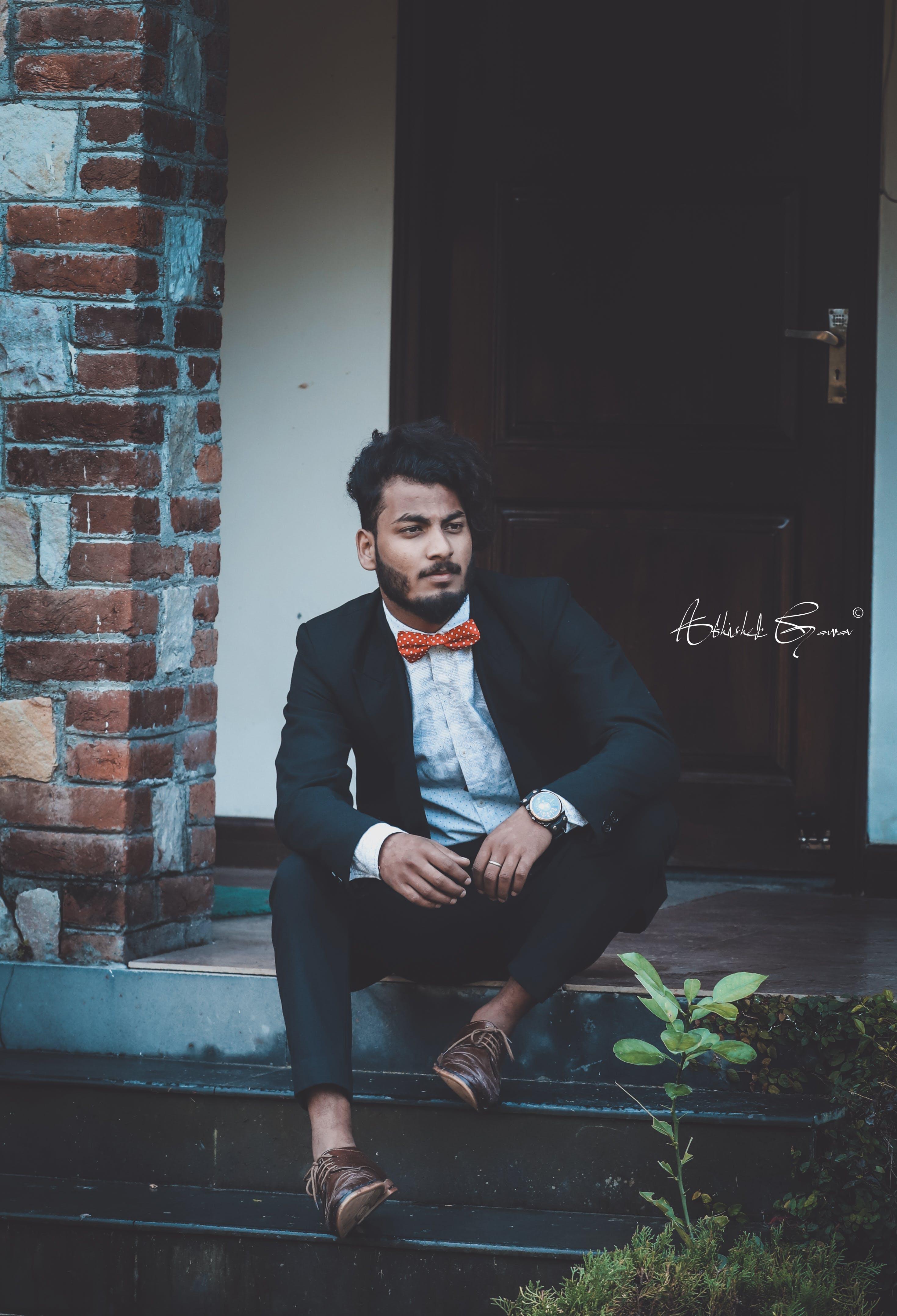 Man Sitting Near Brown Door