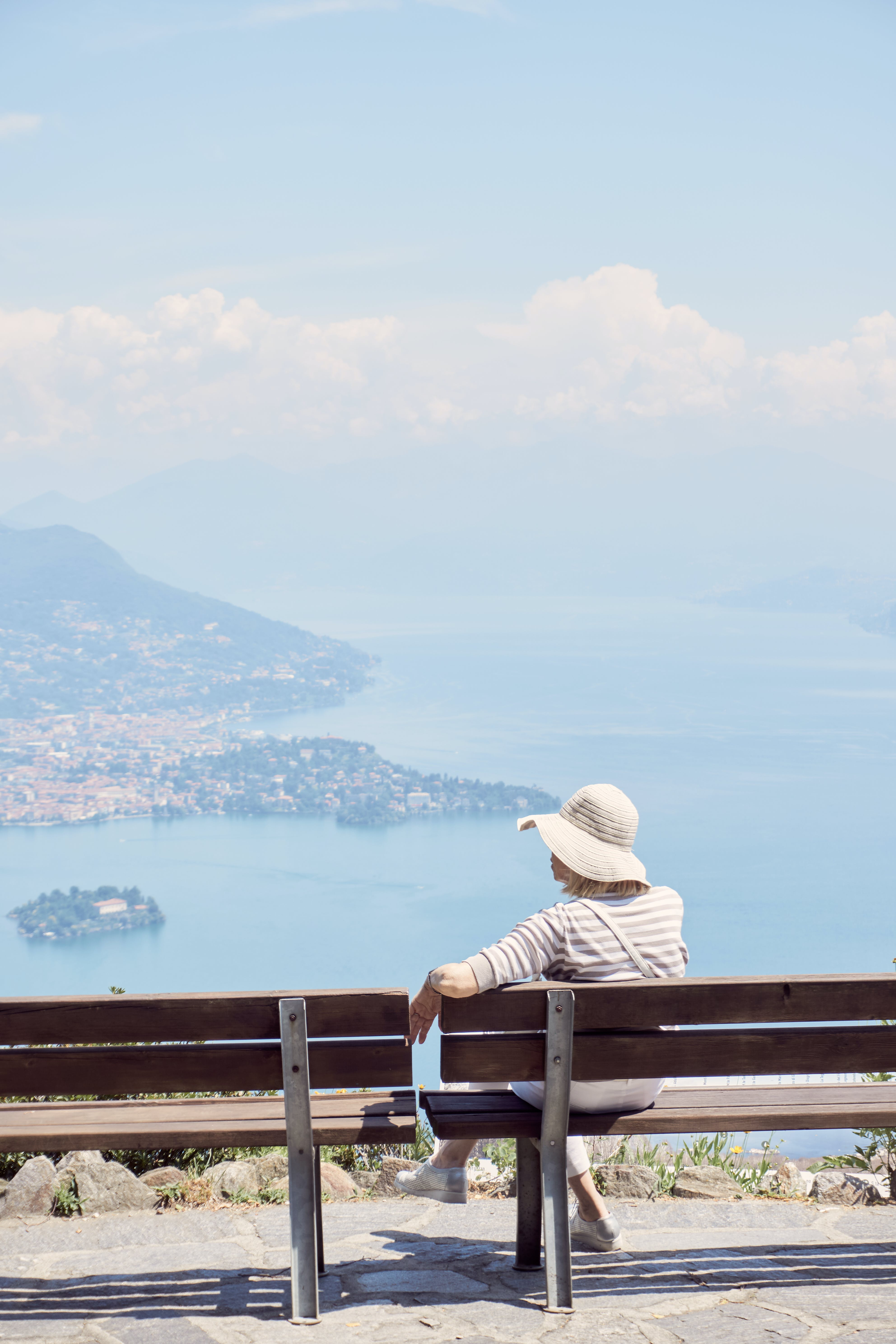 Woman Sitting on Brown Bench Facing Body of Water