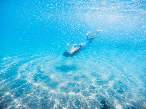 Anonymous male diver swimming in bright blue water during vacation