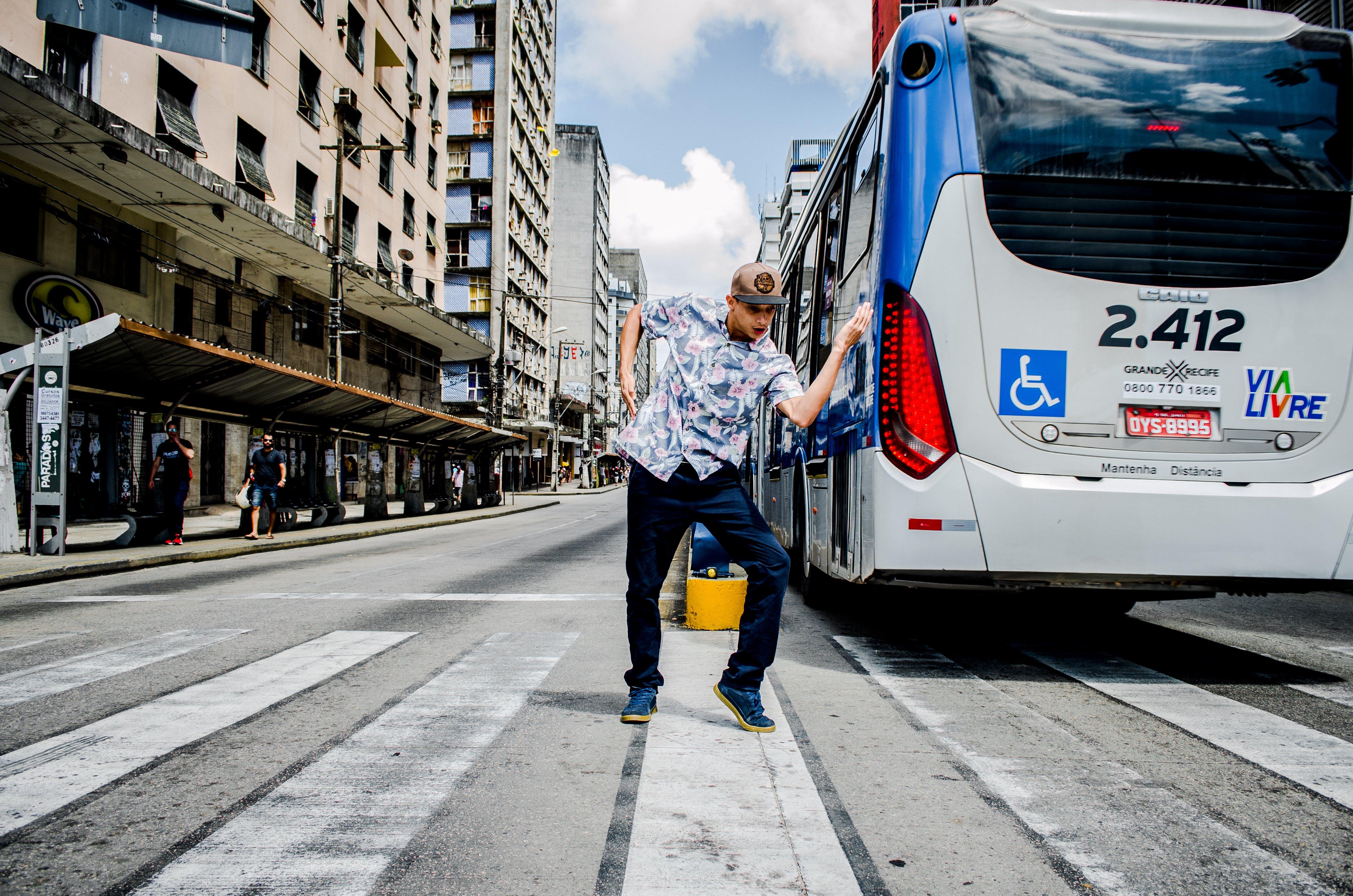 Man Dancing on Pedestrian Crossing Near Bus