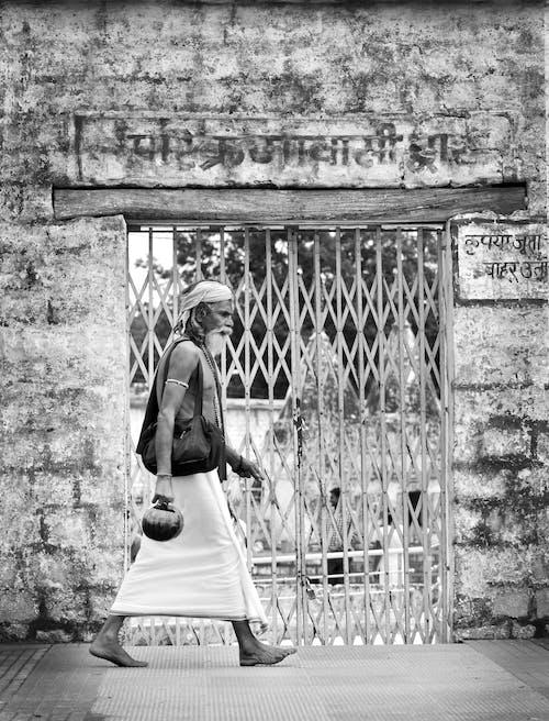 Grayscale Photo of Man Walking Beside Scissor Gate
