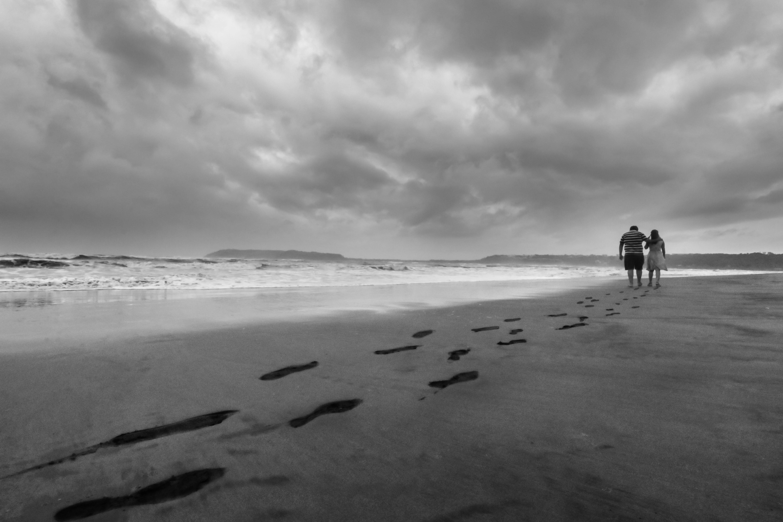Grayscale Photo of Couple Walking on Seashore