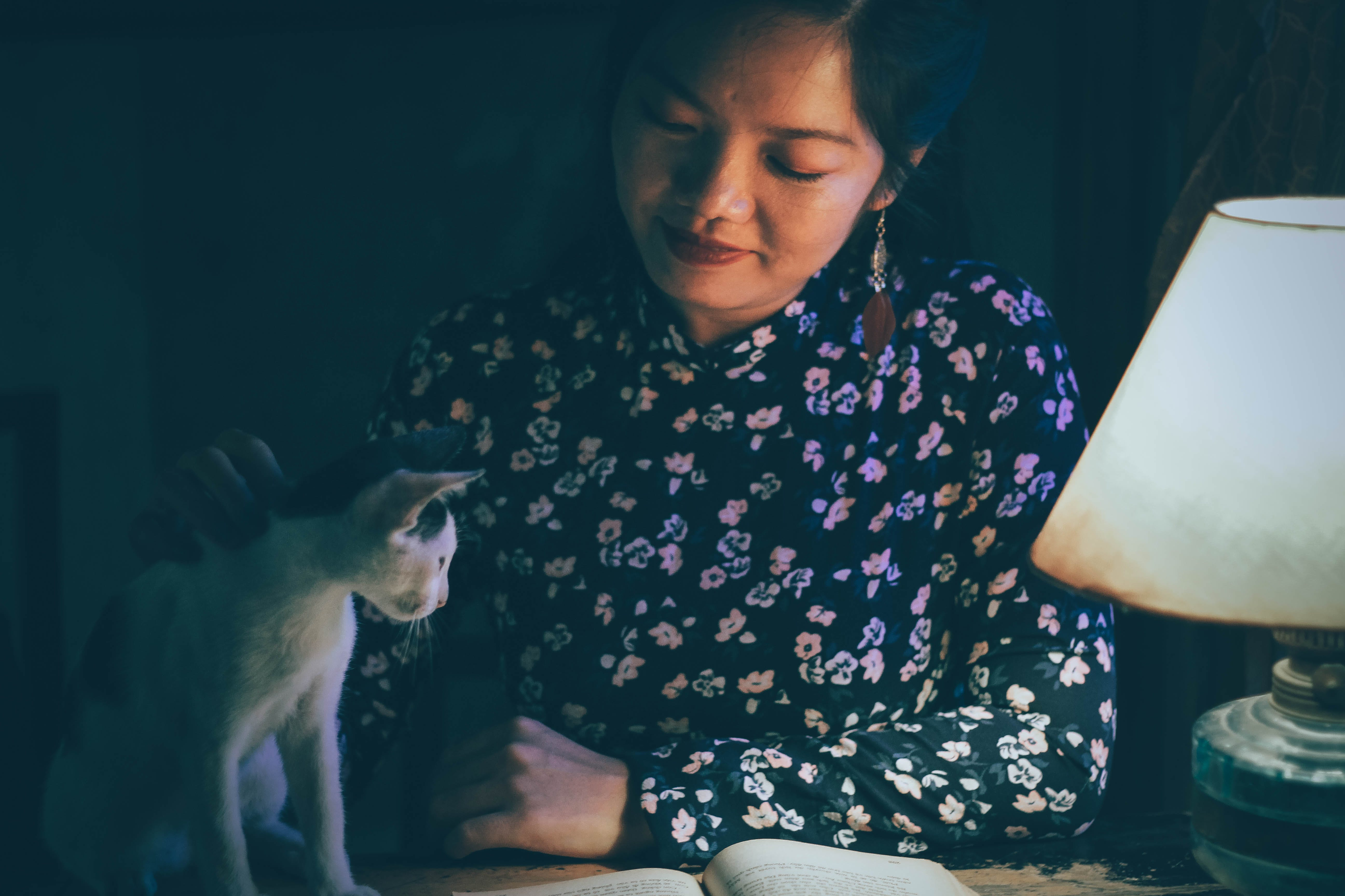 Woman Caressing a Cat While Reading Book Lighted by a Table Lamp in Dark