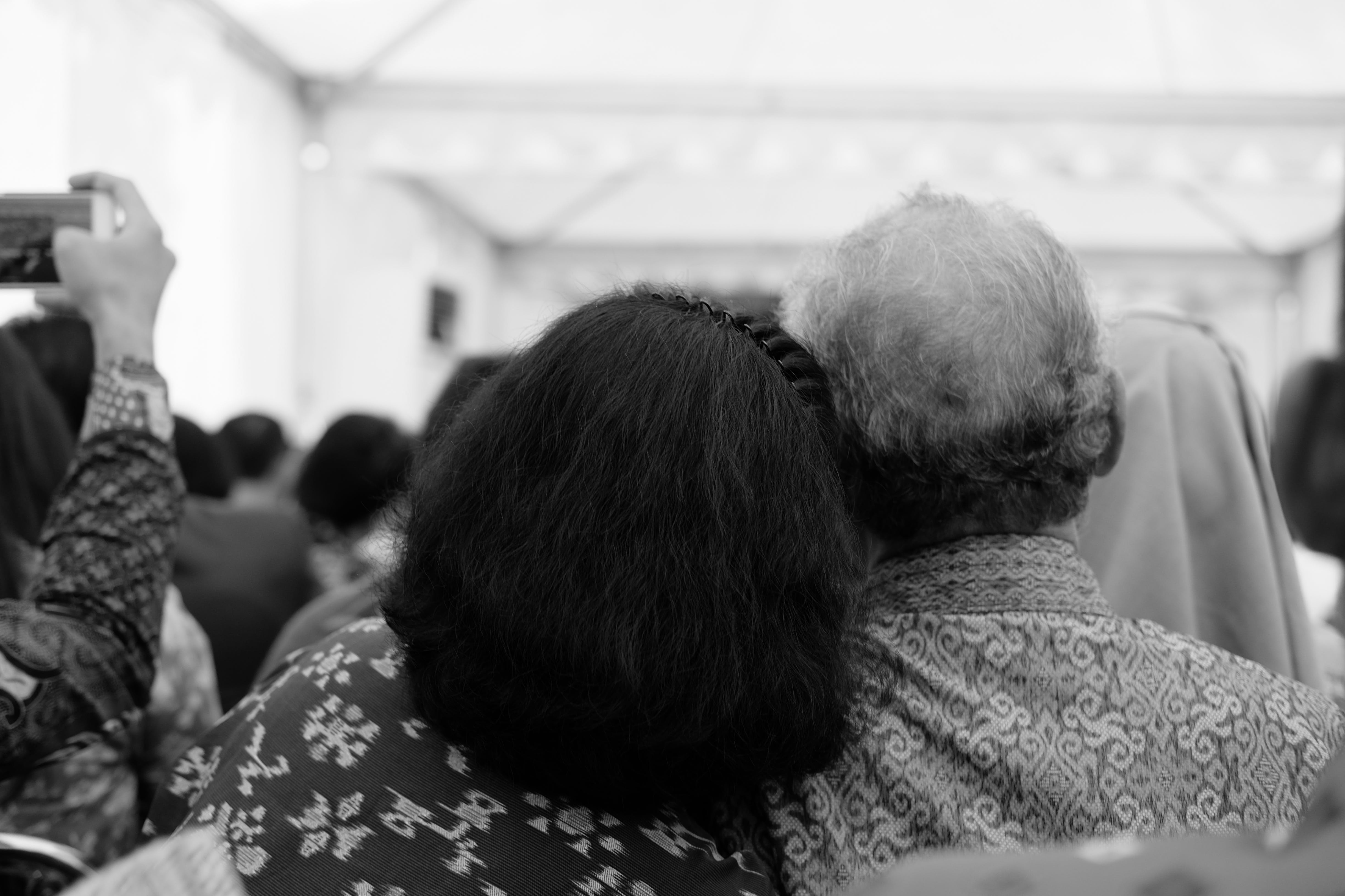 Grayscale Photography of Two Person Resting Their Head on Each Other
