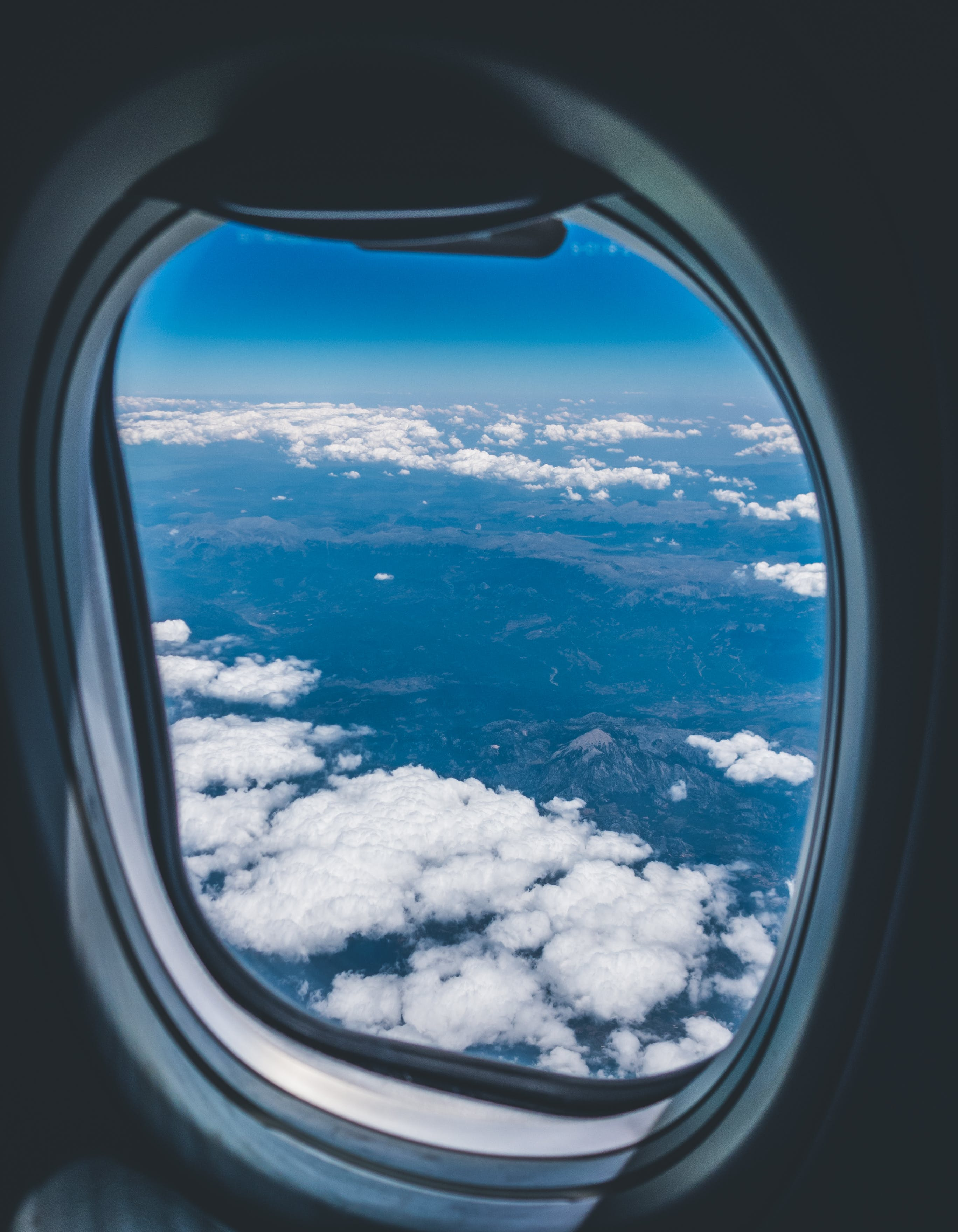 Airplane Window View of White Clouds over Mountain