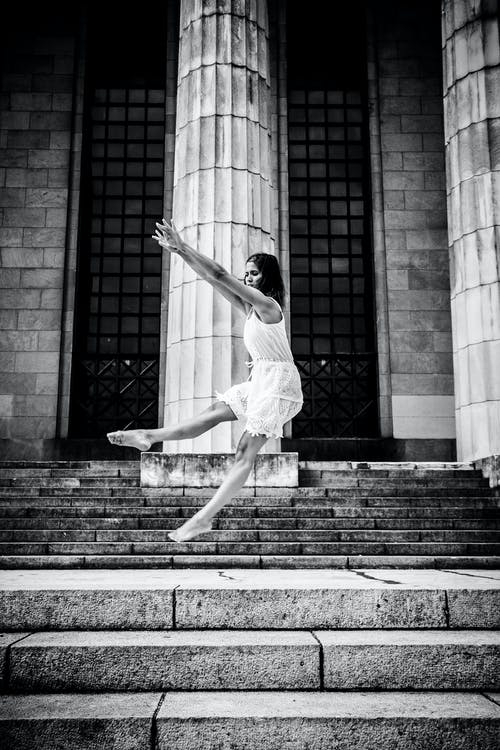 Grayscale Photo Of Woman Dancing On Stairs