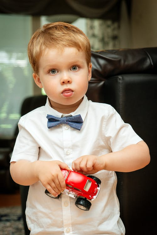 Boy Wearing White Collared Button-up Shirt Holding Red Vehicle Toy