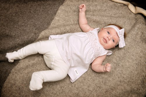 Baby in White Dress Laying on Gray Textile