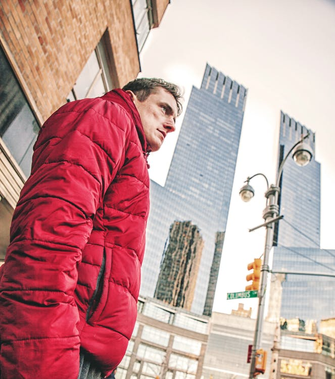Man Wearing Red Bubble Coat Standing Under Tall Buildings