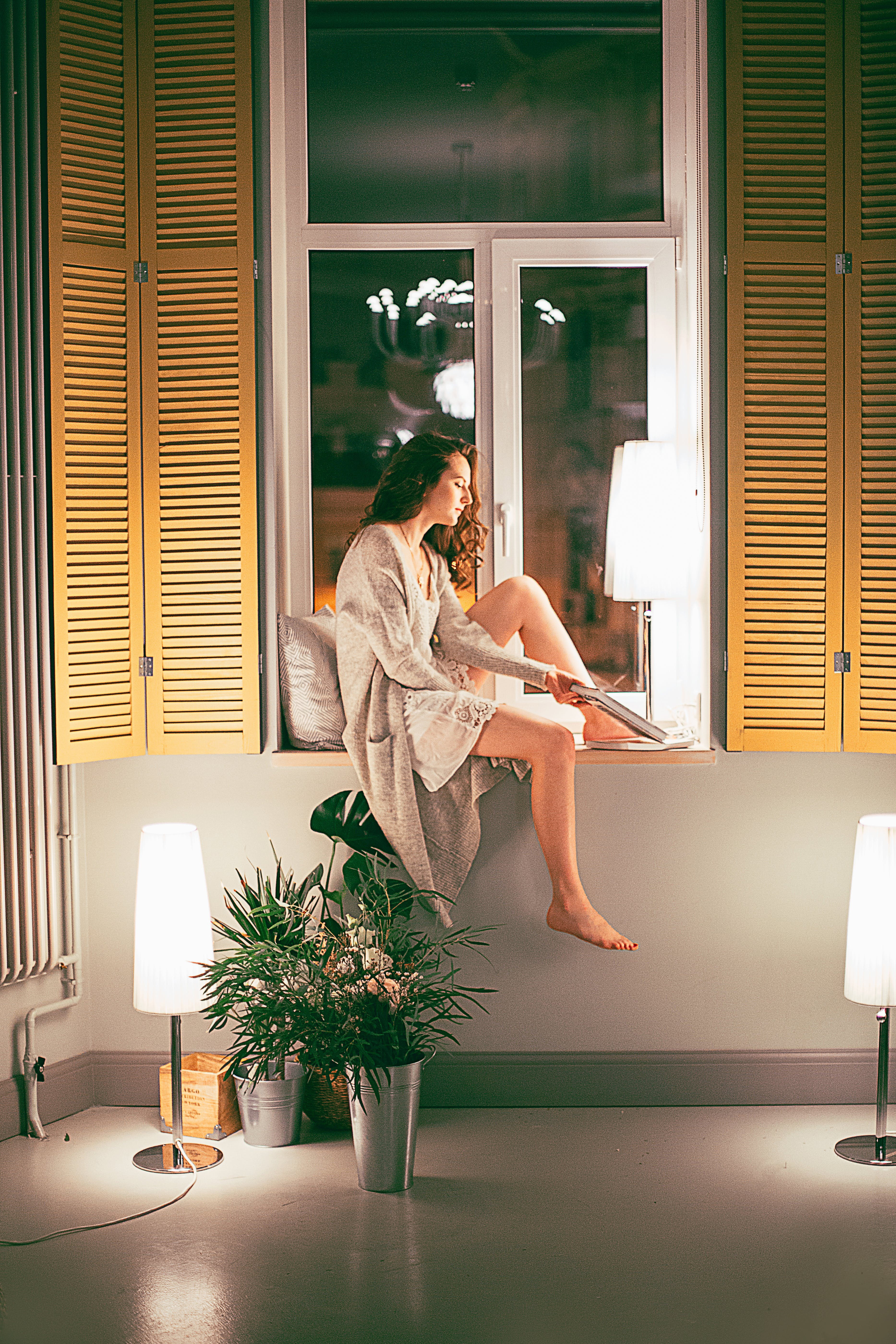 Woman Wearing Cardigan Sitting by the Window at Nighttime