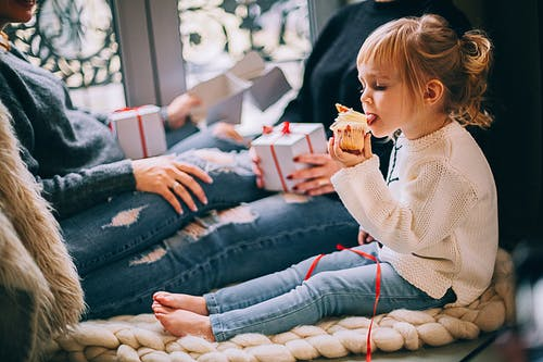 Girl Eating Cupcake While Sitting Beside Woman in Blue Denim Distressed Jeans