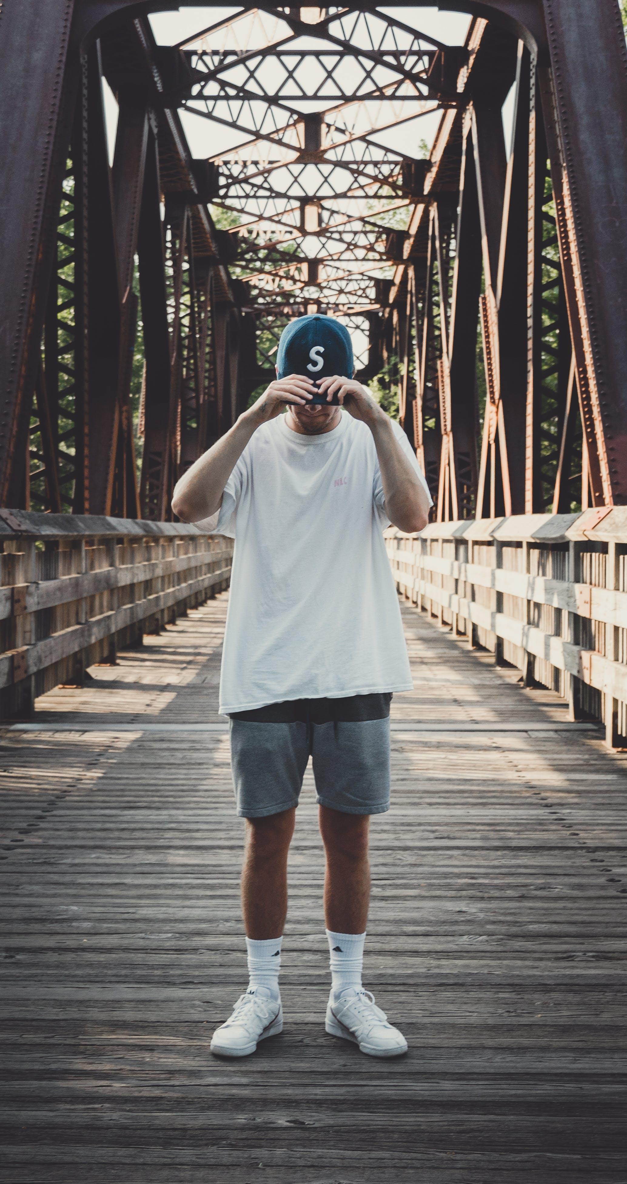 Man in White Crew-neck T-shirt Standing on Bridge