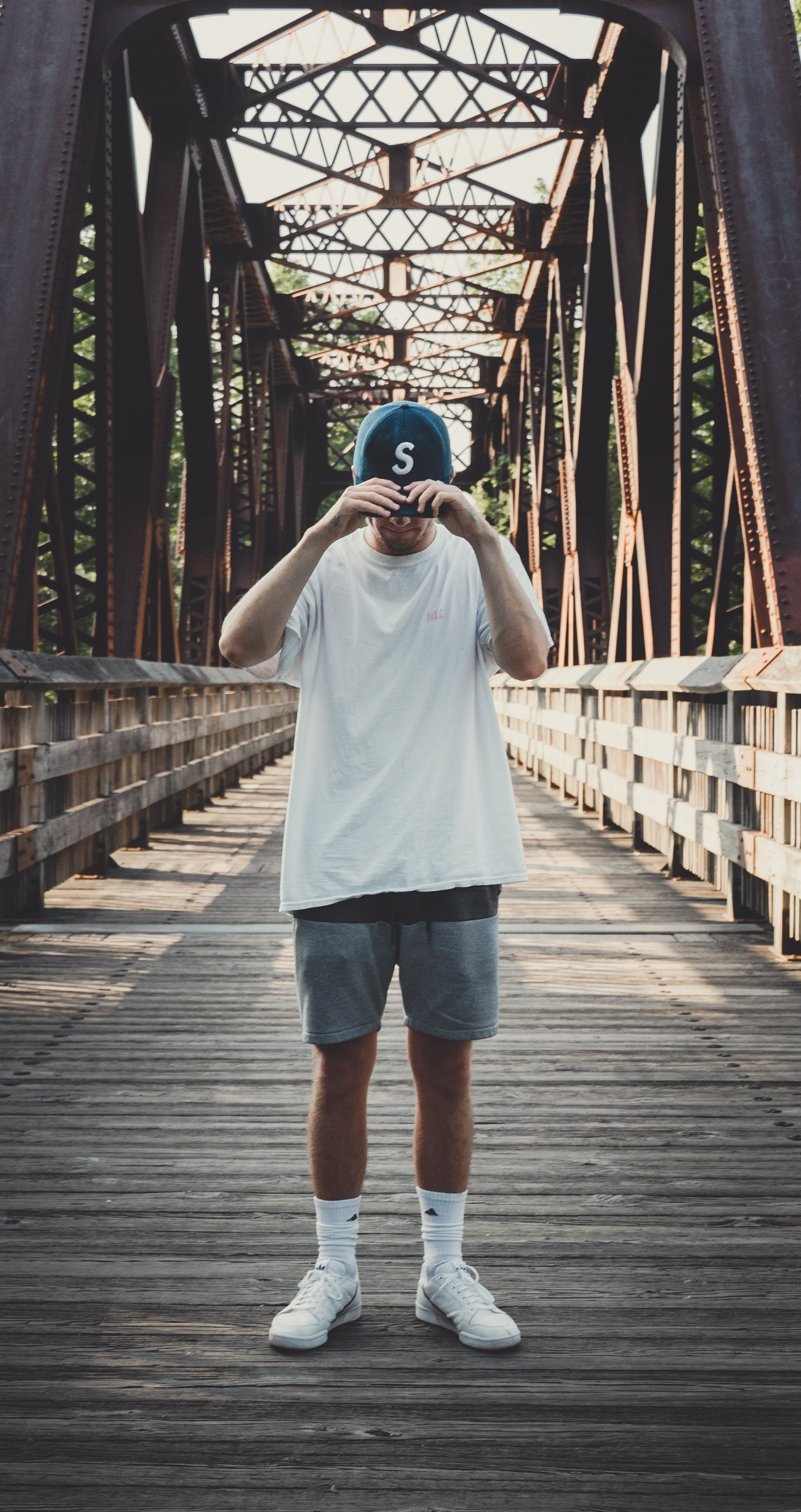 Man in White Crew-neck T-shirt Standing on Bridge