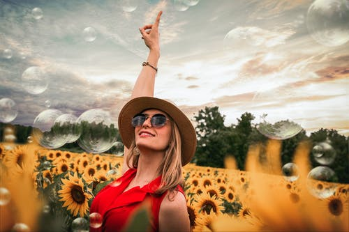 Woman Surrounded by Sunflowers Raising Hand