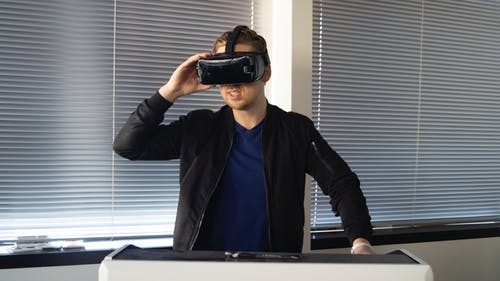 Man Wearing Black Jacket Holding Vr Inside the Room