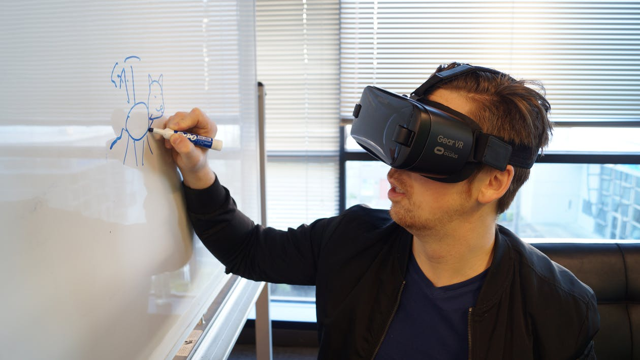 Person Wearing Black Vr Box Writing On White Board