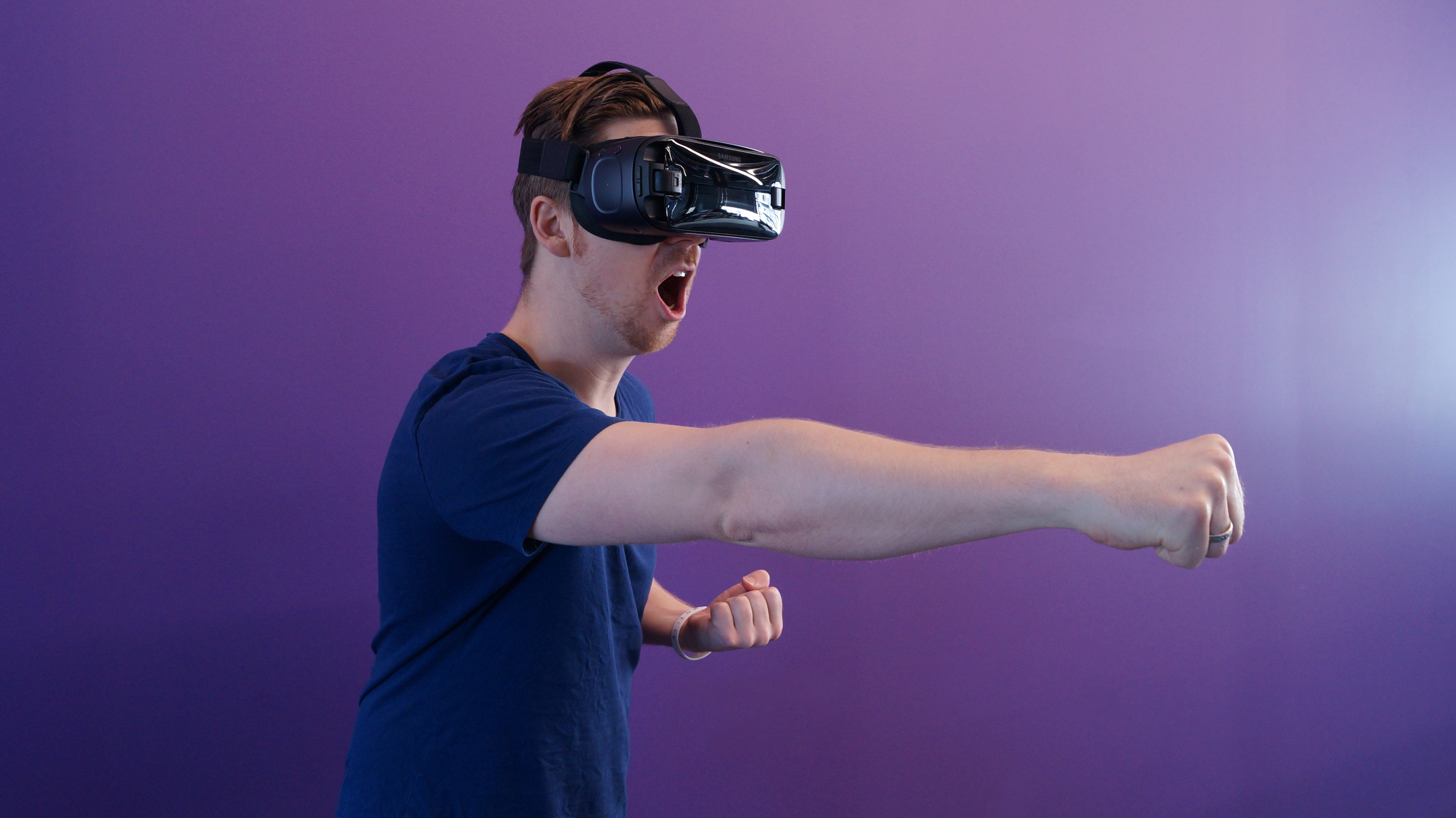 Man punching in the air while wearing VR goggles.