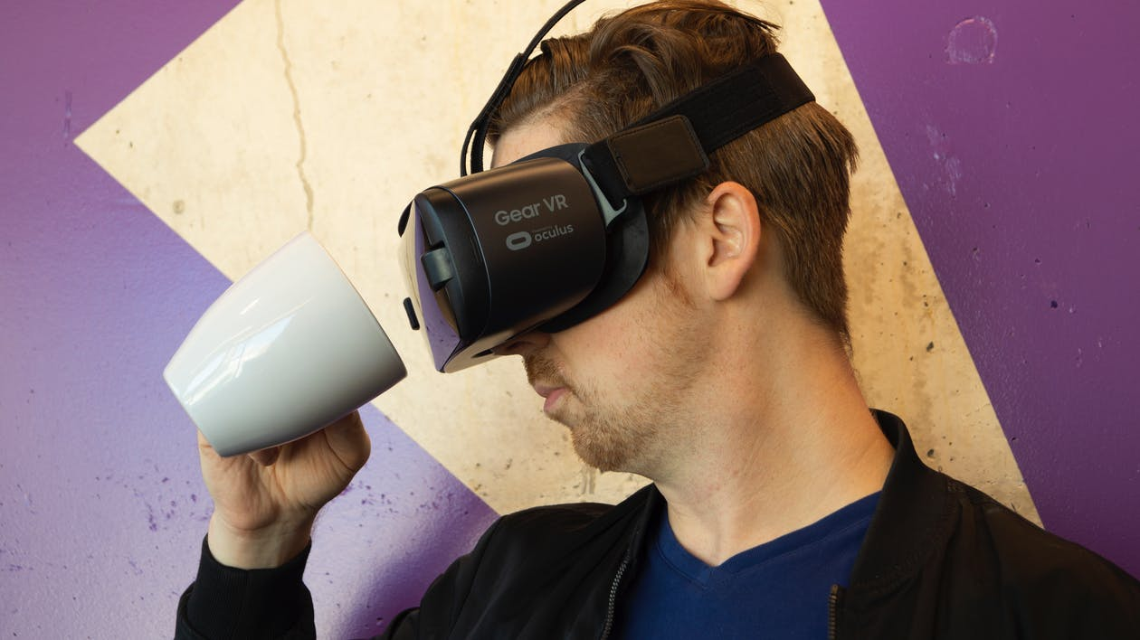 Man Wearing Virtual Reality Headset And Holding A Mug