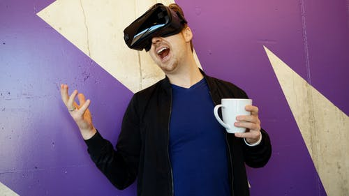 Man Wearing Black Virtual Reality Headset While Holding White Mug