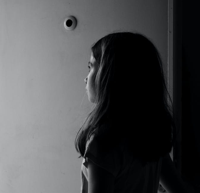 Grayscale Photography of Girl Near Wall