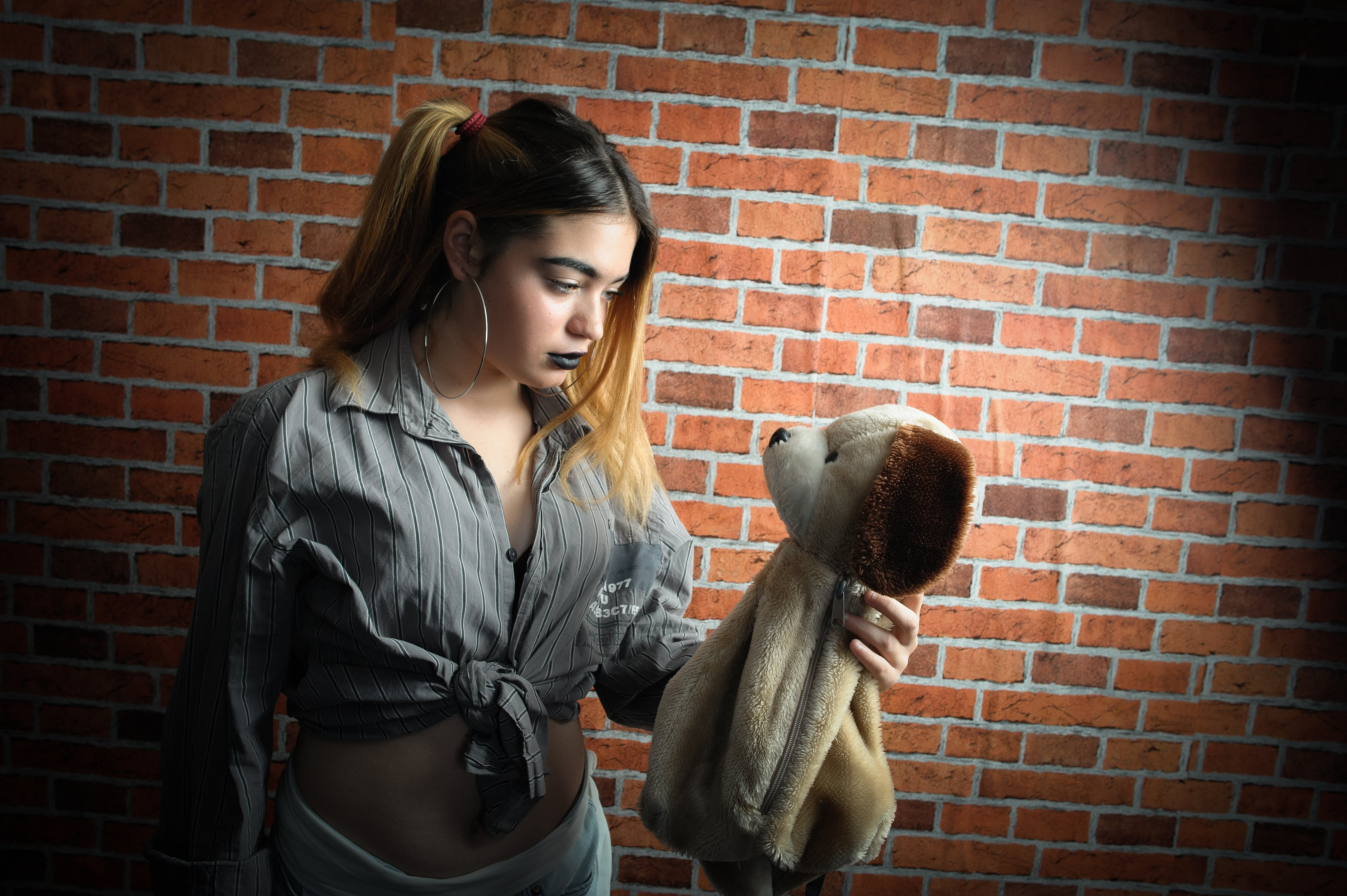 Woman Looking and Holding Brown Dog Plush Toy