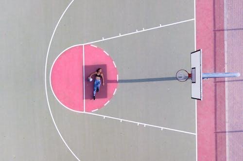 Woman Lying on Basketball Free Throw Line