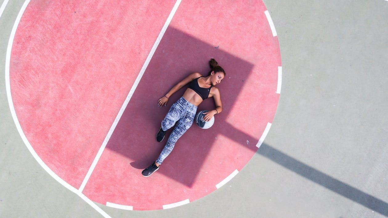Woman Lying on Basketball Court