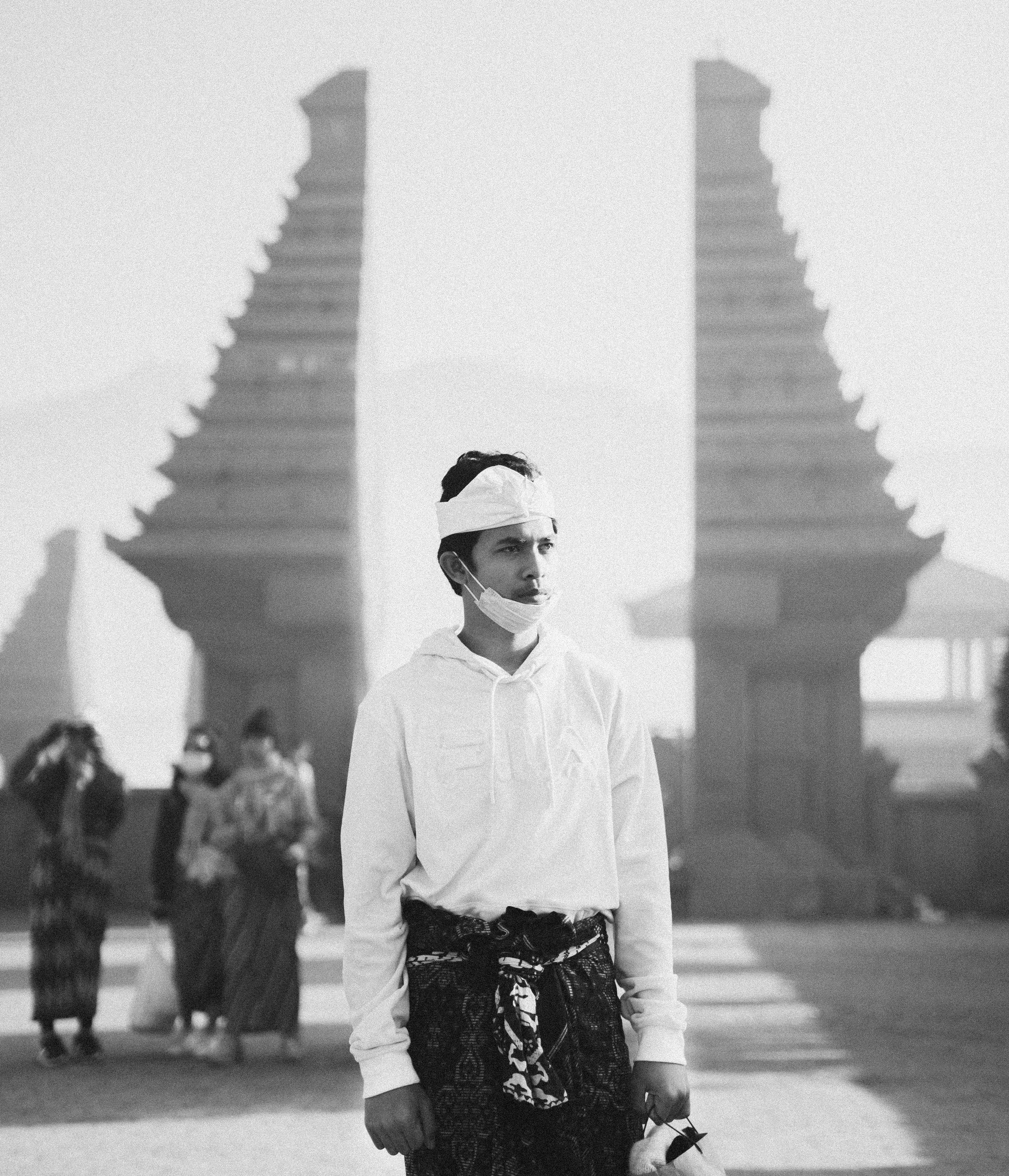 Grayscale Photography of Man Standing in Between of Pillars