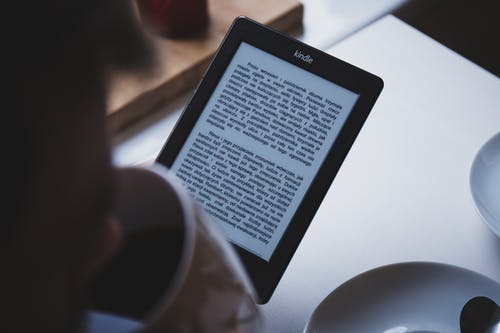 Person Using E-book Reader While Drinking Coffee
