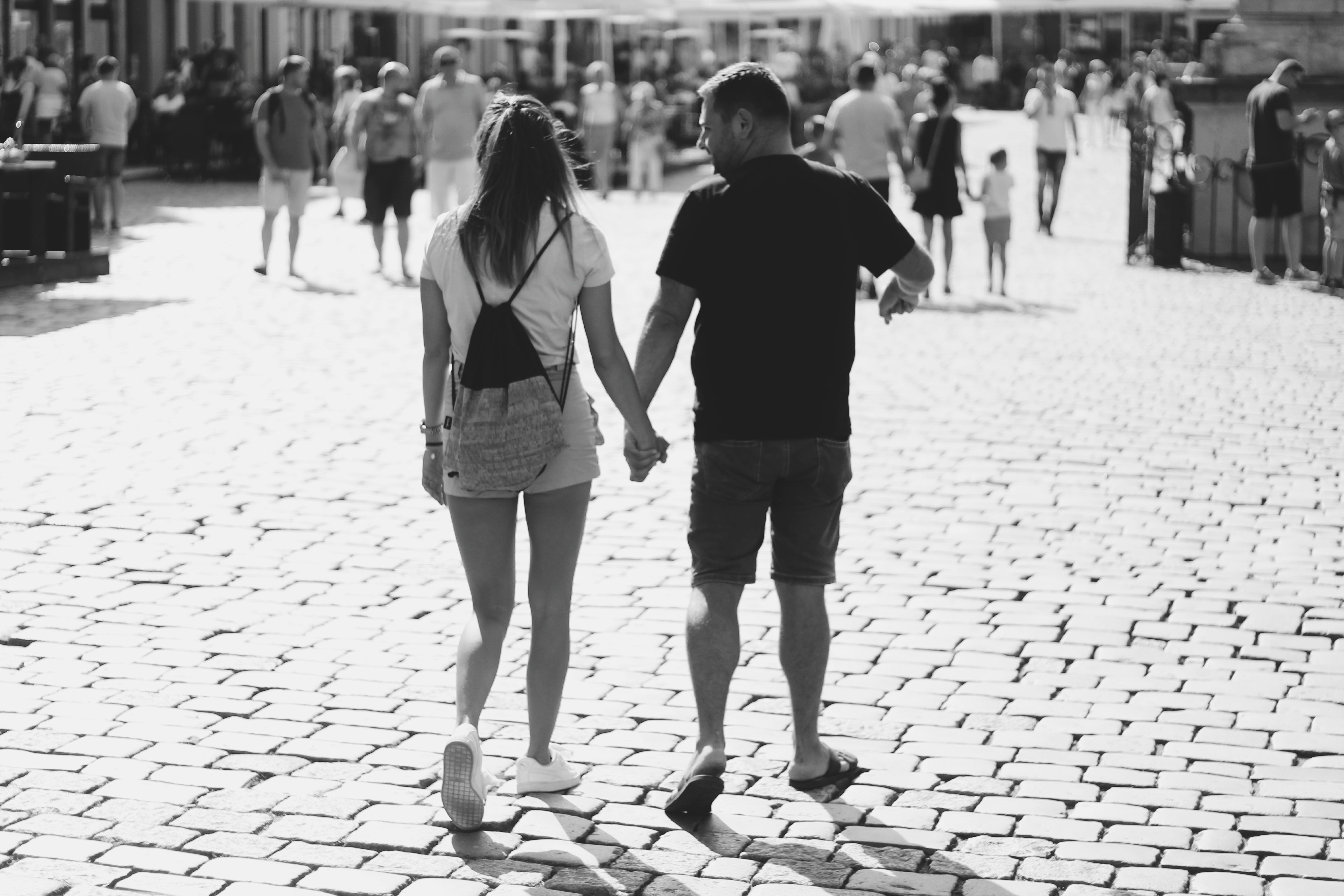 Grayscale Photography of Woman and Man Holding Hands While Walker