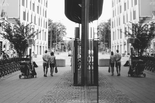 Grayscale Photography Of Man And Woman Walking At The Street