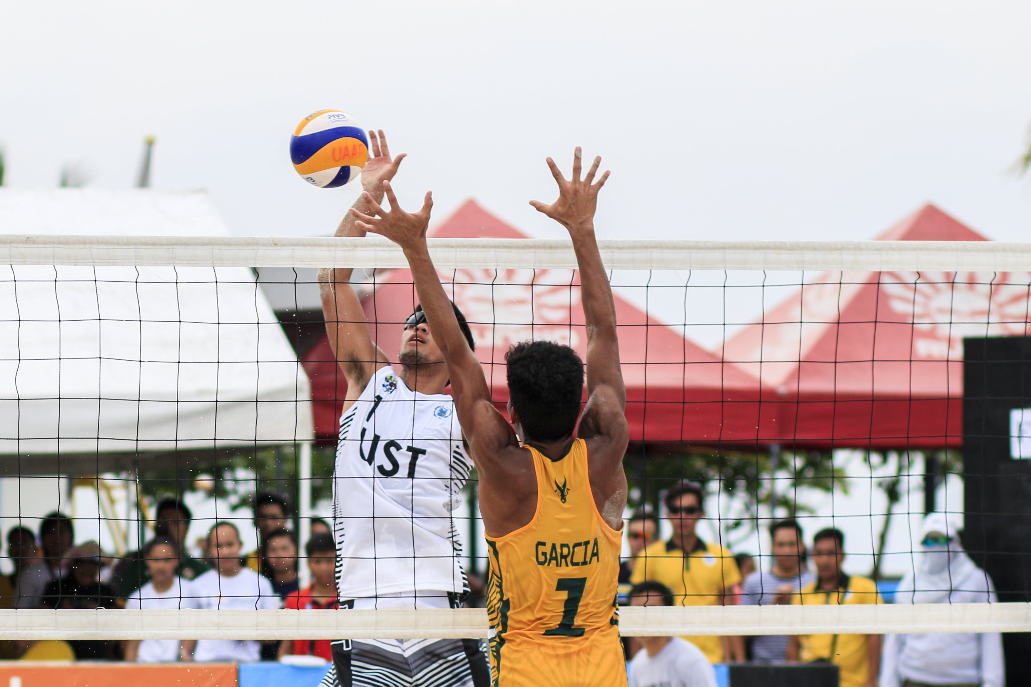 Two Men Playing Volleyball Near Red Canopy