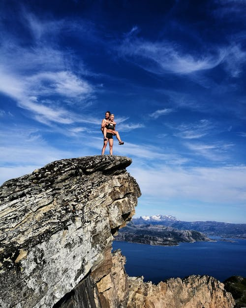 Landscape Photography of Two Persons on Cliff