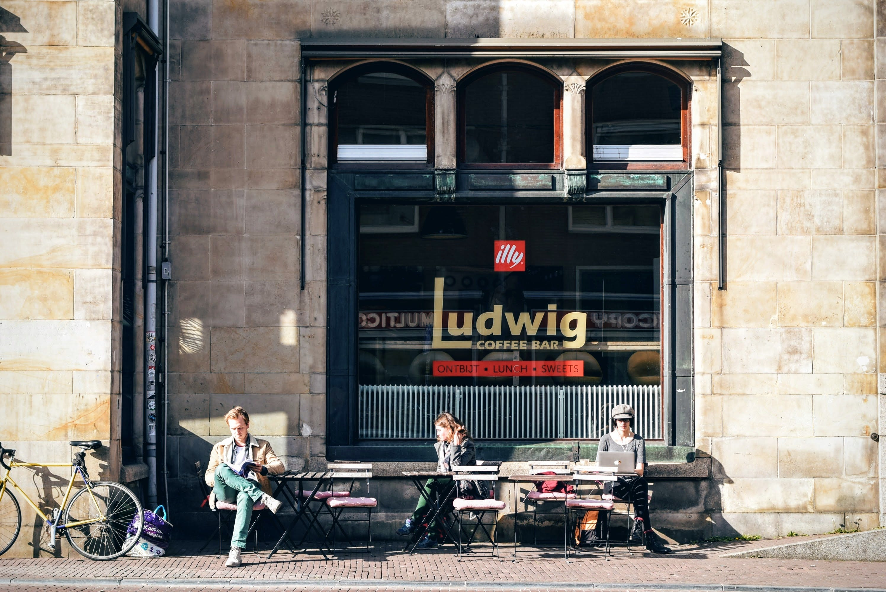 Three People Sitting on Bench in Front of Ludwig Coffee Bar