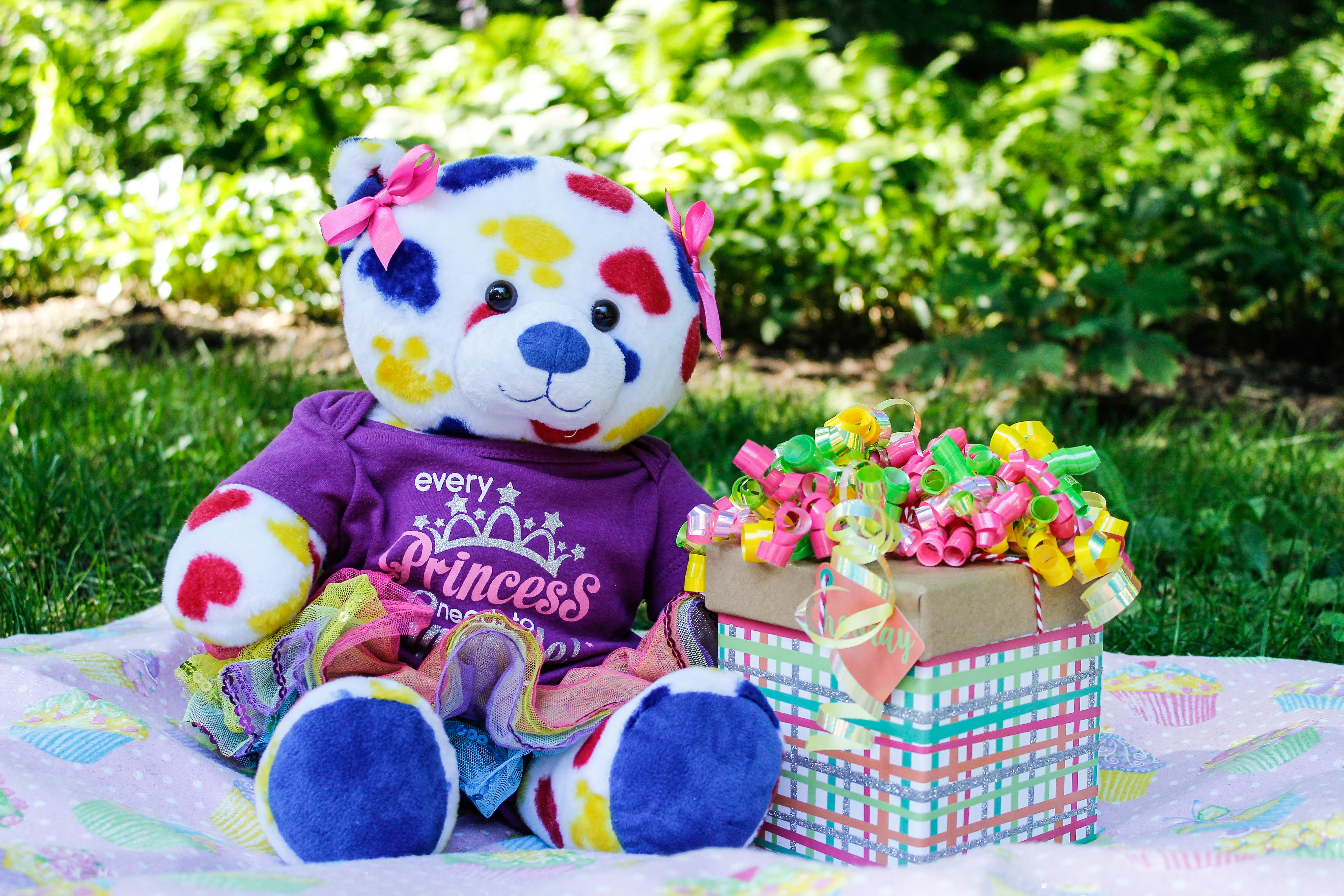 White, Yellow, Red, and Blue Teddy Bear Beside Gift Box