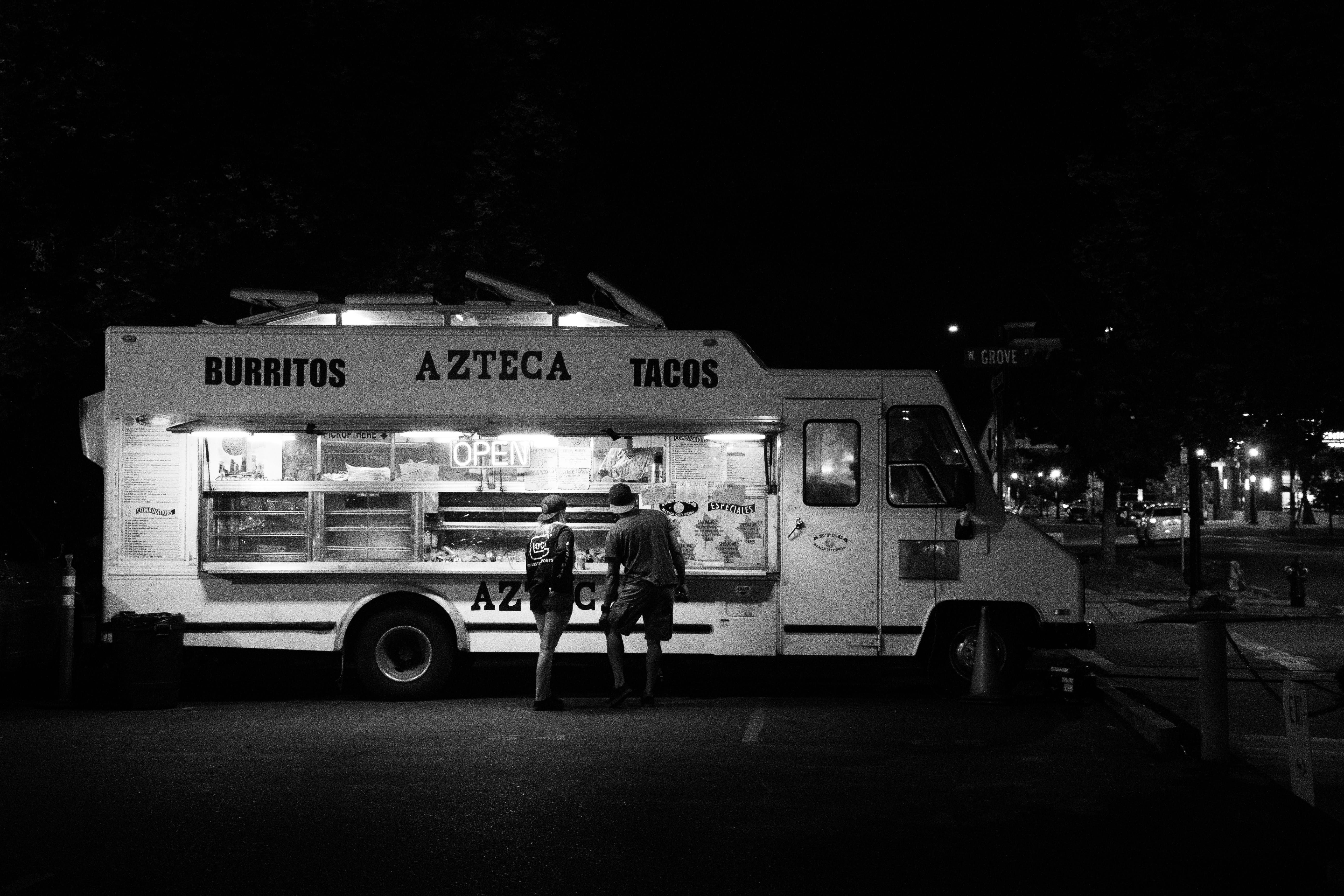 Grayscale Photograph of Two People Standing in Front of Food Truck