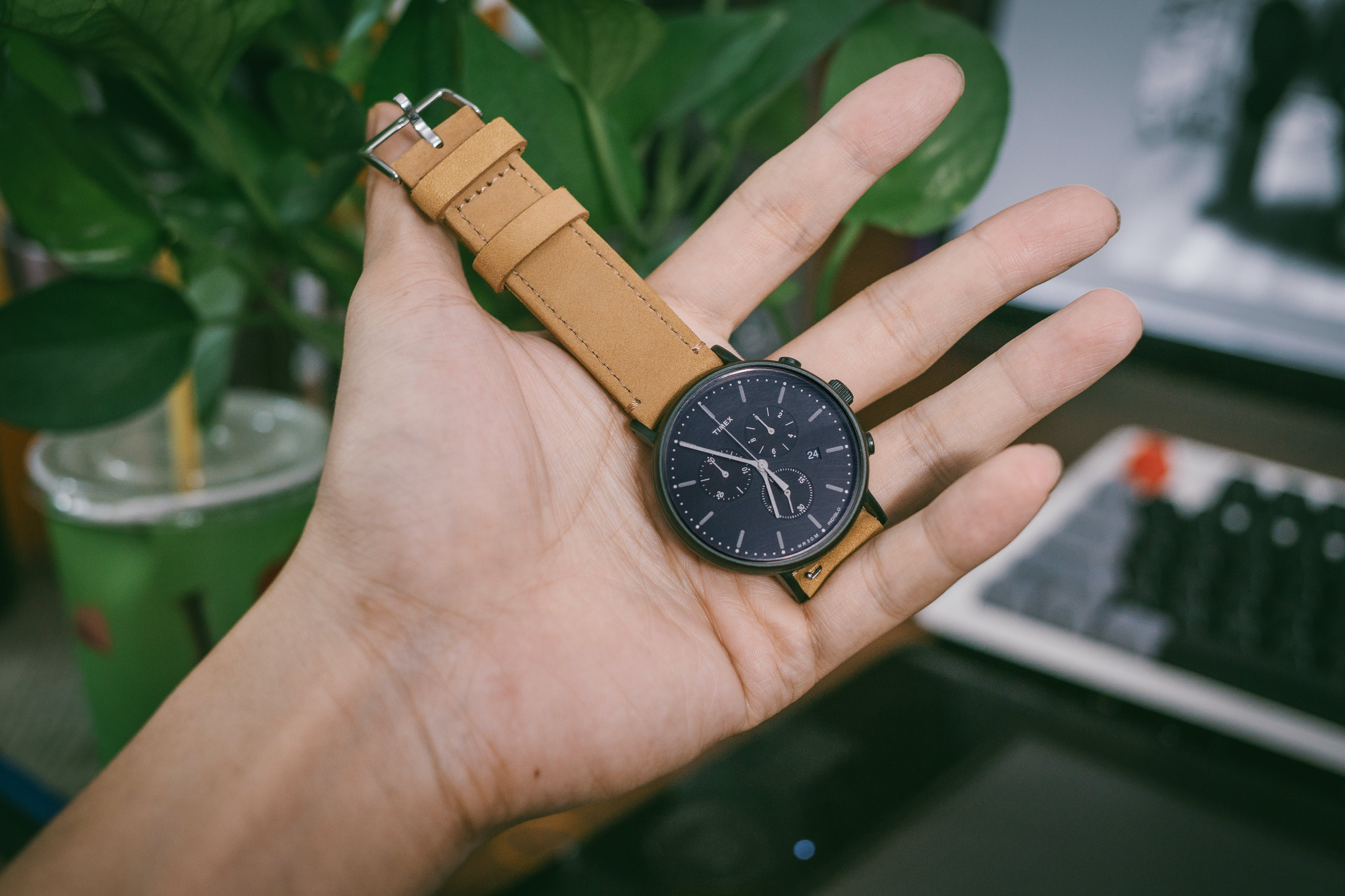 Person Holding Black Chronograph Watch With Brown Leather Strap