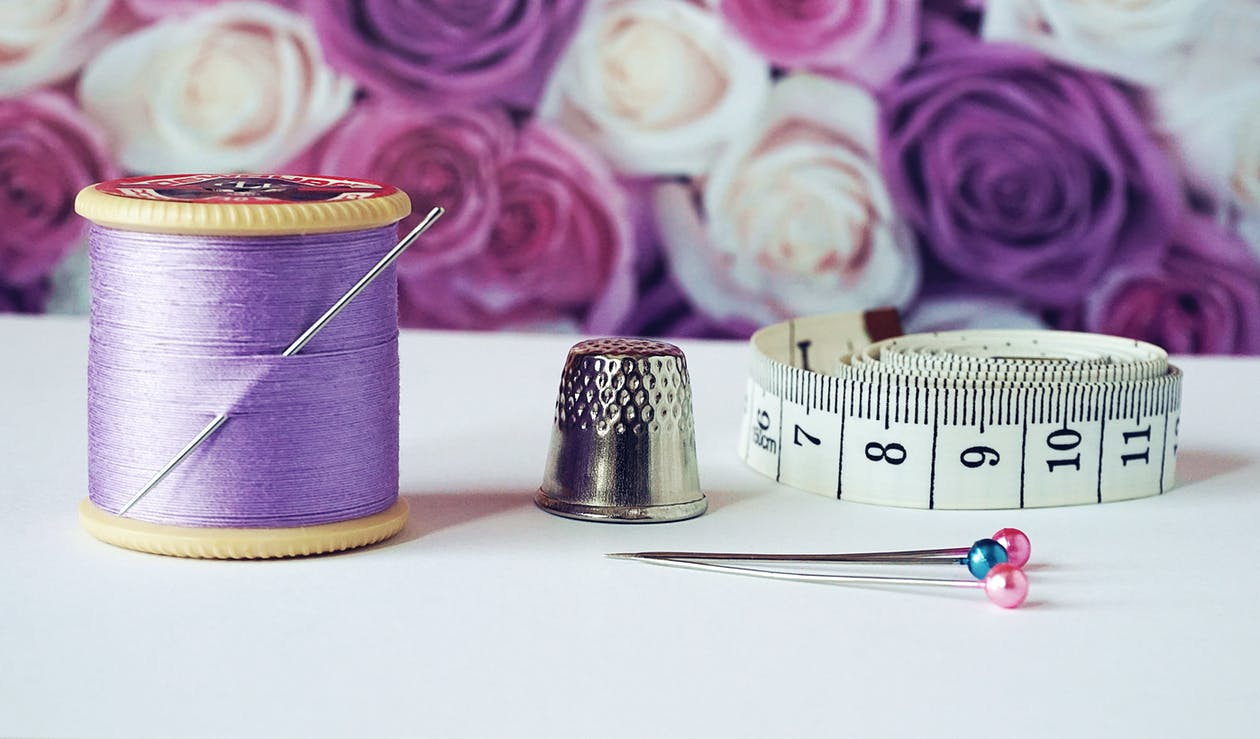 Spool of Purple Thread Near Needle Thimble and Measuring Tape