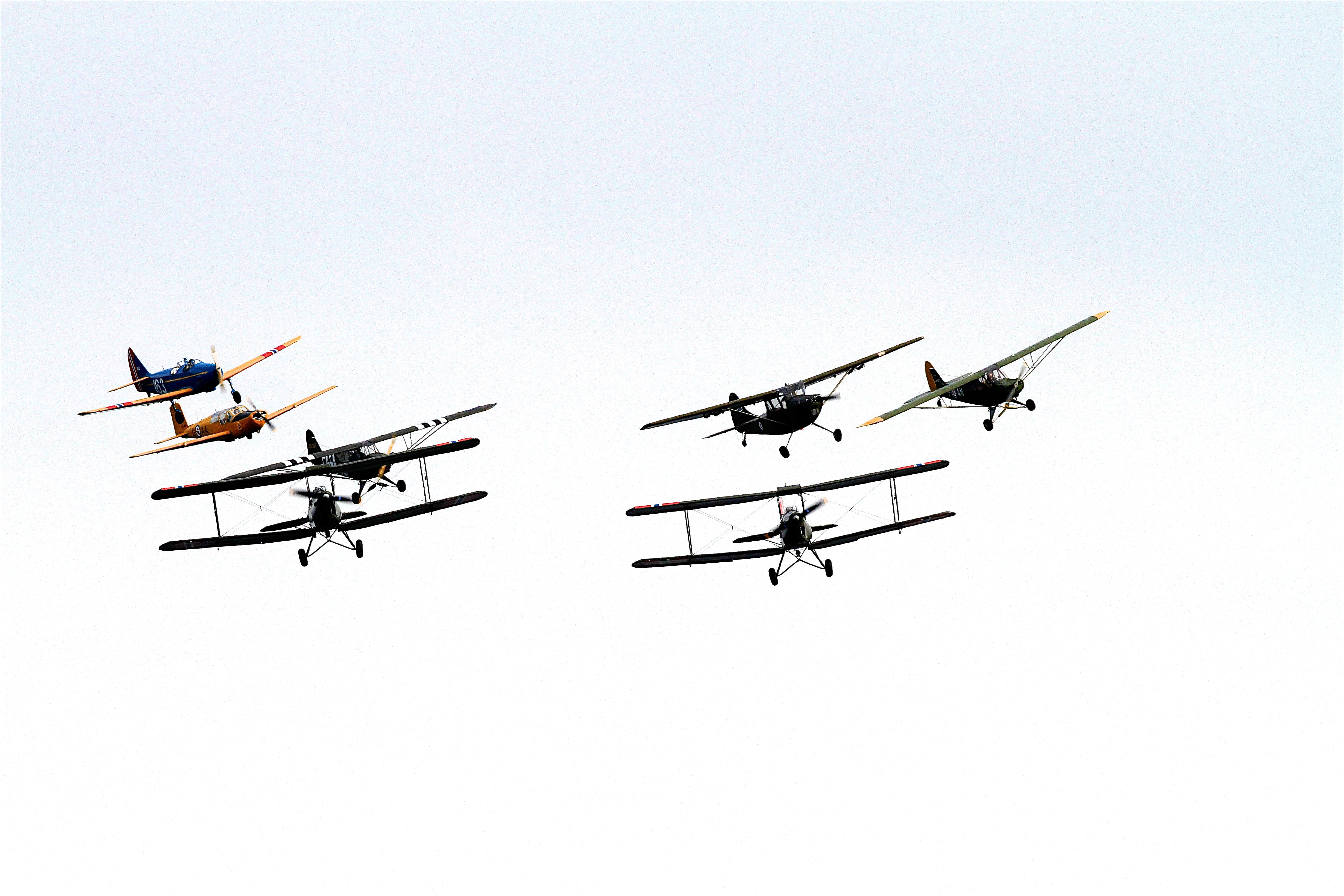 7 Biplane Flying on Air Under Clouds during Daytime
