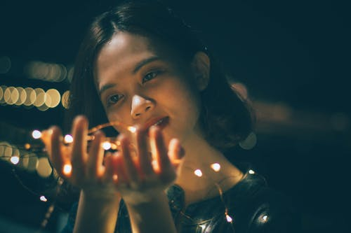 Close-Up Photography of Woman Holding String Lights